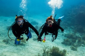 Two divers swimming hand in hand on one of our dive trips